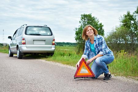emergency sign: Woman installing emergency sign on road near broken car