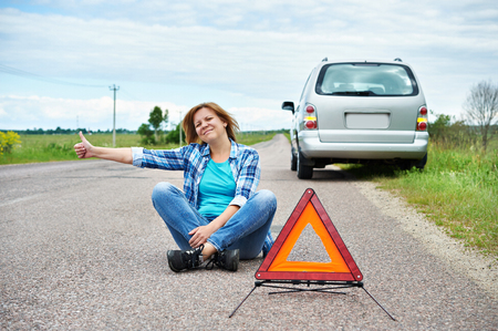 emergency sign: Woman sitting on road near emergency sign and showing thumbs up