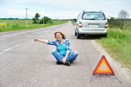 emergency sign: Emotional woman sitting on road near emergency sign and showing thumbs up