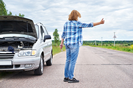 Woman with wrench waiting to help and showing thumbs up near her broken car Stock Photo
