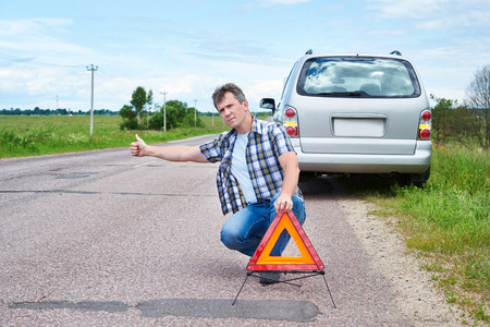 emergency sign: Man sitting on road near emergency sign and showing thumbs up