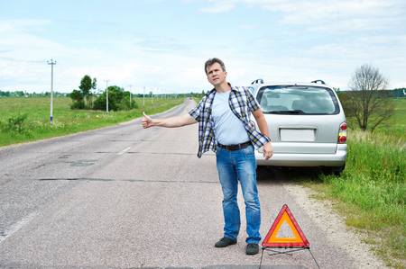 emergency sign: Man standing on road near emergency sign and showing thumbs up Stock Photo