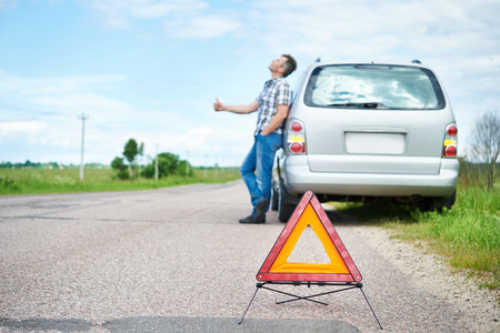 emergency sign: Emergency sign and man standing on road near car waiting help