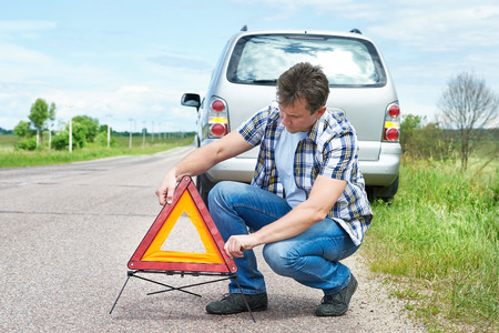 emergency sign: Man installing emergency sign on road near his car waiting help
