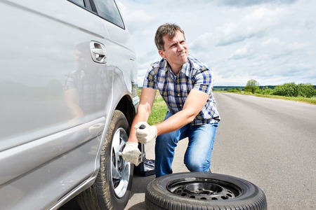 Man changing a spare tire of car on road Stock Photo