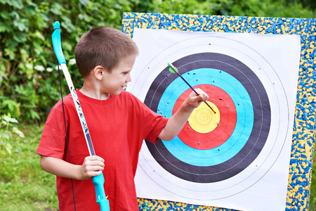 pull out: Little archer with bow pull out arrow from aim outdoors