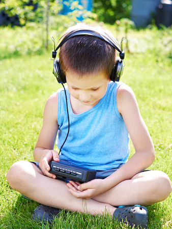 Little boy with old audio cassette player and headphones