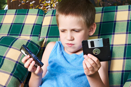 Floppy disk: Little boy with floppy disk and audio cassette outdoors Stock Photo