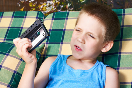 Little boy with old audio cassette