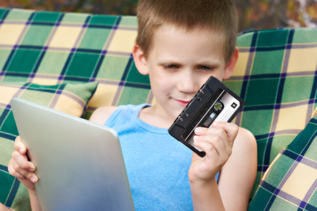 electronic 80s: Little boy with tablet and old audio cassette