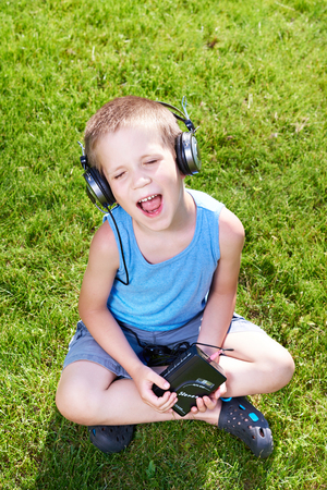 audio cassette: Little boy with old audio cassette player and headphones
