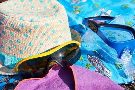 swim mask: Swim mask, hat, sunglasses and a towel on the beach