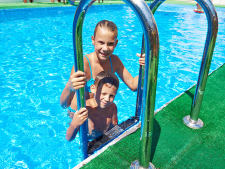 Girl and boy in a resort swimming pool Stock Photo