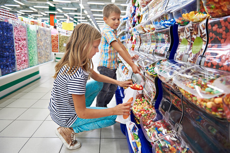 Children buy gummi candy in shop