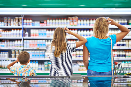 Mother and children are choosing dairy products in shop Stockfoto