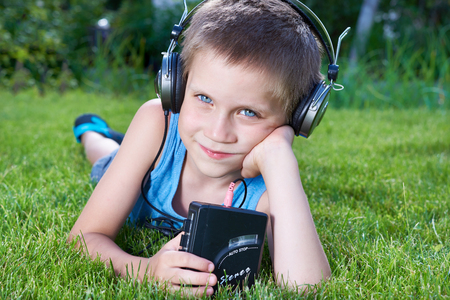 Little boy with old audio cassette player and headphones on grass Stock Photo