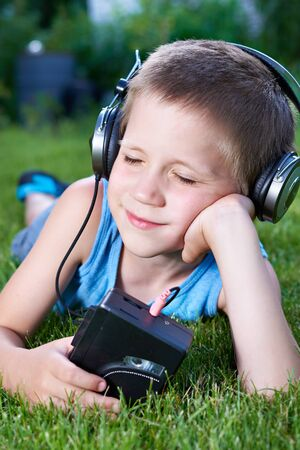 Little boy lying on grass with old audio cassette player and headphones
