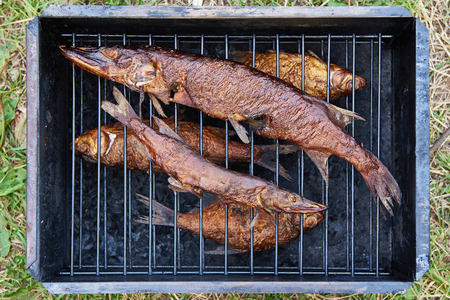 Smoked fish pike and roach in smokehouse Stock Photo