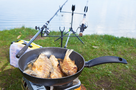 Preparation of fried fish  in pan outdoors on fishing