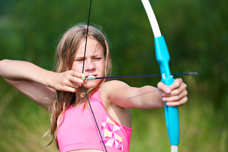 Girl teenager with a bow nock and aims Фото со стока