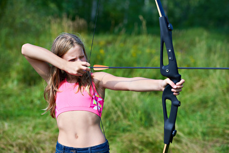 Girl teenager with a bow nock and aims Stock Photo