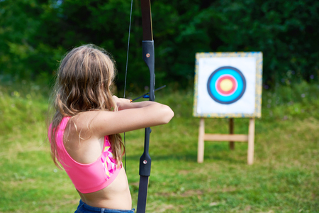 Girl teenager with a bow nock and aims to target Stock Photo
