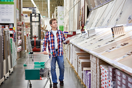 floorboard: Man chooses floorboard for home renovation in store