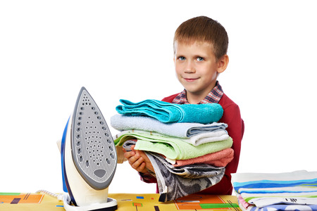 difficult lives: Boy with washed linen around the ironing board with iron isolated white