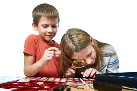 Niño y la niña están considerando la colección de monedas aislado en blanco Foto de archivo
