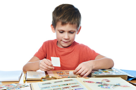 postage stamps: Boy with his collection of old postage stamps isolated white