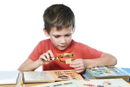 stamp collection: Boy with magnifying glass looks his stamp collection isolated white Stock Photo