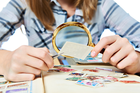 stamp collection: Teen girl with magnifier looks his stamp collection Stock Photo