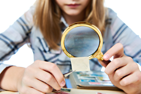 Teen girl with magnifying glass looks his stamp collection