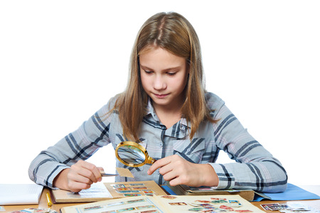 stamp collection: Teen girl with magnifying glass looks his stamp collection isolated white