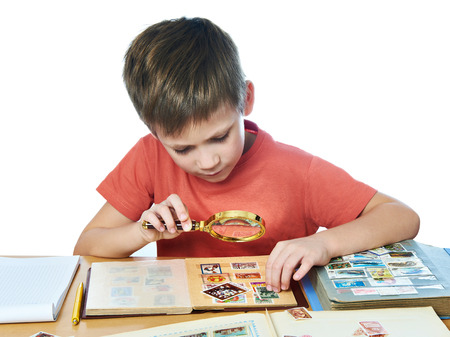 Boy with magnifying glass looks his stamp collection isolated white Stock Photo