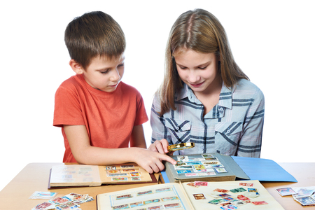 stamp collection: Teen girl and little boy with magnifying glass looking his stamp collection isolated white