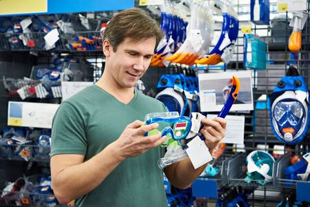 water sports: Man chooses a mask for scuba diving in the store