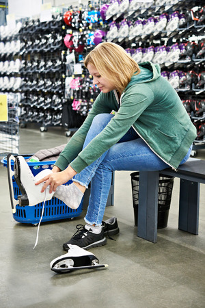 Woman trying on figure skates in the sports shop Stock Photo