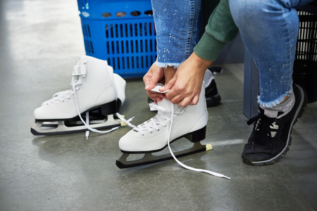 Woman laces figure skates in the sports shop