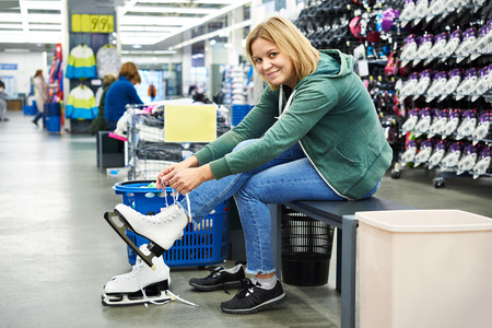 Happy woman trying on figure skates in the sports shop Stock Photo