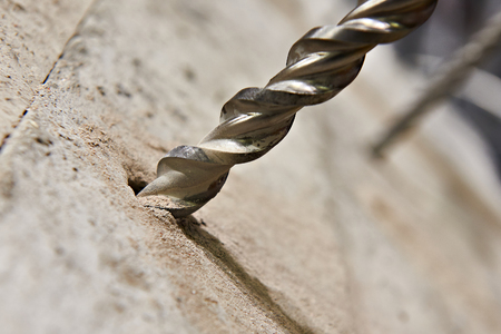 コンクリートのクローズ アップの穴に大きなドリル ビット