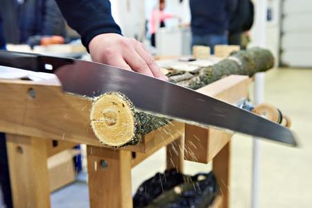 serrucho: El hombre serrar madera sierra de mano en una mesa de carpintería