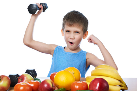 Healthy sporty boy with fruits, vegetables and dumbbells isolated white Фото со стока