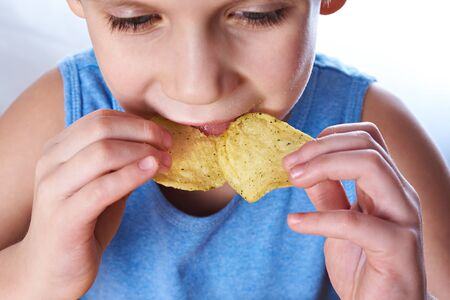unwholesome: Little boy eating potato chips closeup
