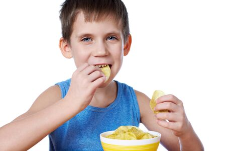 unwholesome: Little boy eating potato chips isolated white Stock Photo