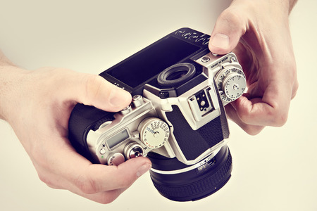 Retro SLR camera in the hands of the photographer closeup Stock Photo