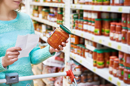 gamme de produit: Woman chooses lecho tomato at the grocery store