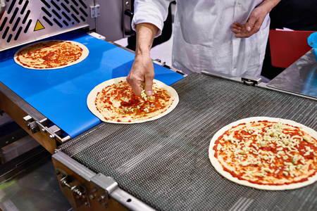 adds: Worker cook adds cheese to the pizza on the conveyor