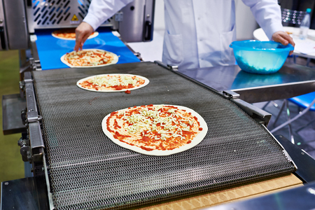adds: Worker baker cook adds cheese to the pizza on the conveyor Stock Photo