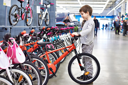 Boy chooses a bicycle in a sports supermarket